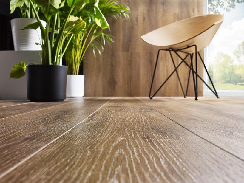 eleganckie nowoczesne krzesło zpołączonym siedziskiem ioparciem wjedną drewnianą owalną część na brązowej drewnianej podłodze