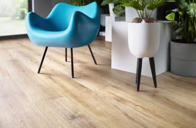 niebieskie plastikowe krzesło na drewnianych nogach na eleganckiej jasnej drewnianej podłodze