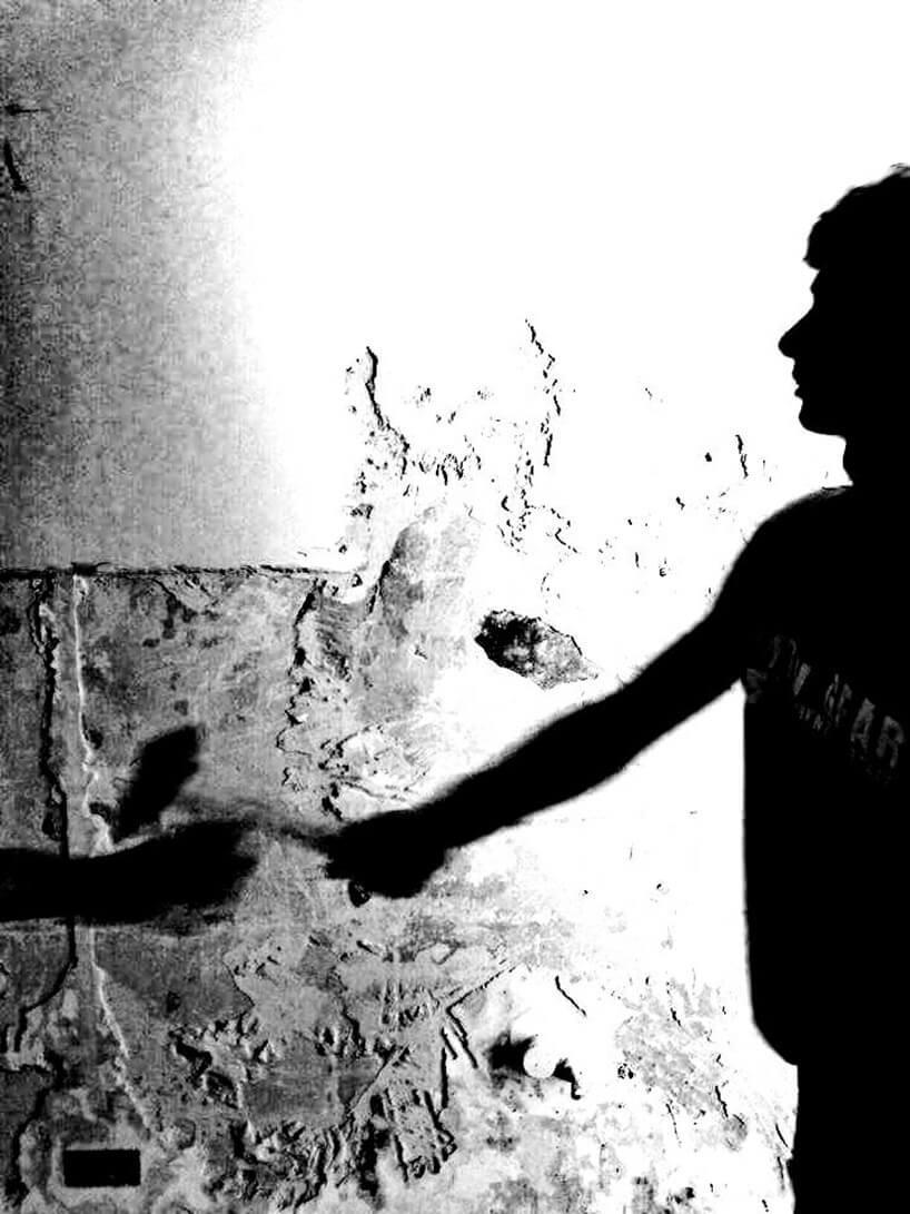 czarno-białe zdjęcie mężczyzny skrobiącego ścianę zfarby