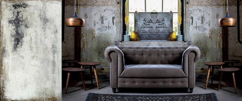 szara sofa we wnętrzu zodrapanymi ścianami