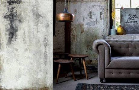 szara sofa we wnętrzu z odrapanymi ścianami