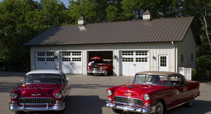 dwa stare samochody przed białym garażem