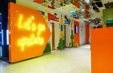 wnętrze hotelu ibis i żywych kolorach i neonem Let's go upstairs