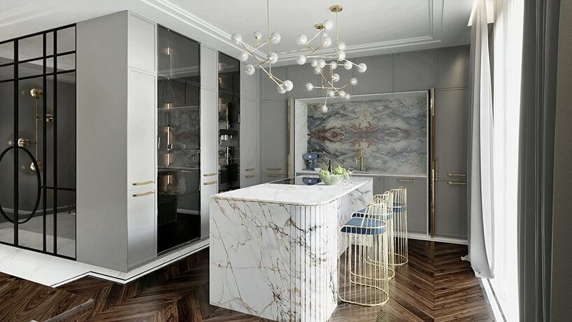 nieduża kuchnia zszarymi szafkami idużą wyspą zbiałego kamienia ztrzema wysokimi złotymi krzesłami