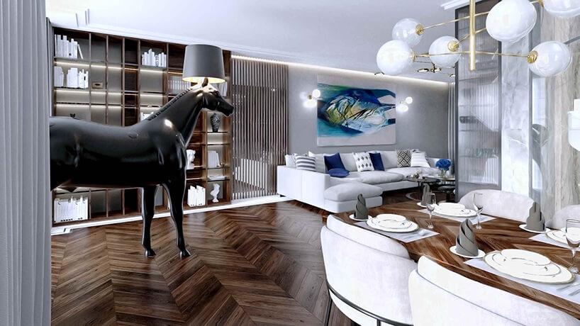elegancki jasny salon zciemną drewnianą podłogą zdużą narożną sofą ilampą na głowie konia
