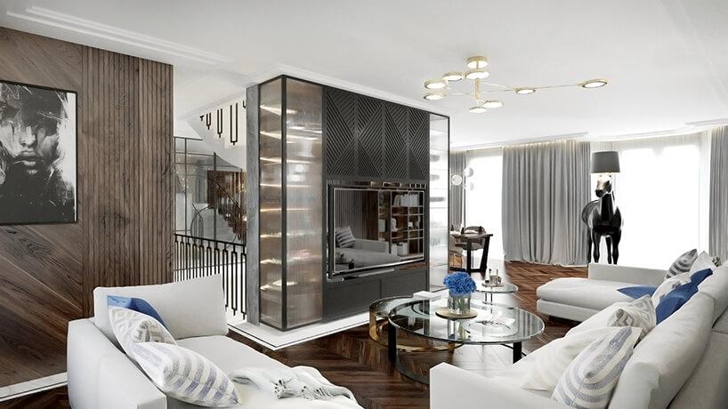 elegancki jasny salon zciemną drewnianą podłogą zdużą narożną sofą zszarą zabudową wokół telewizora