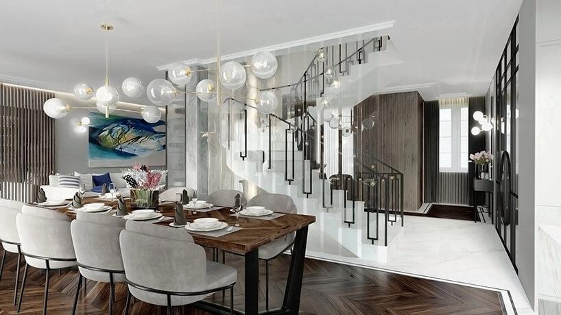 duży drewniany stół zjasno szarymi krzesłami na tle białych schodów zczarną poręczą