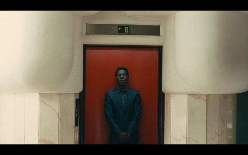 mężczyzna stojący na tle czerwonych drzwi