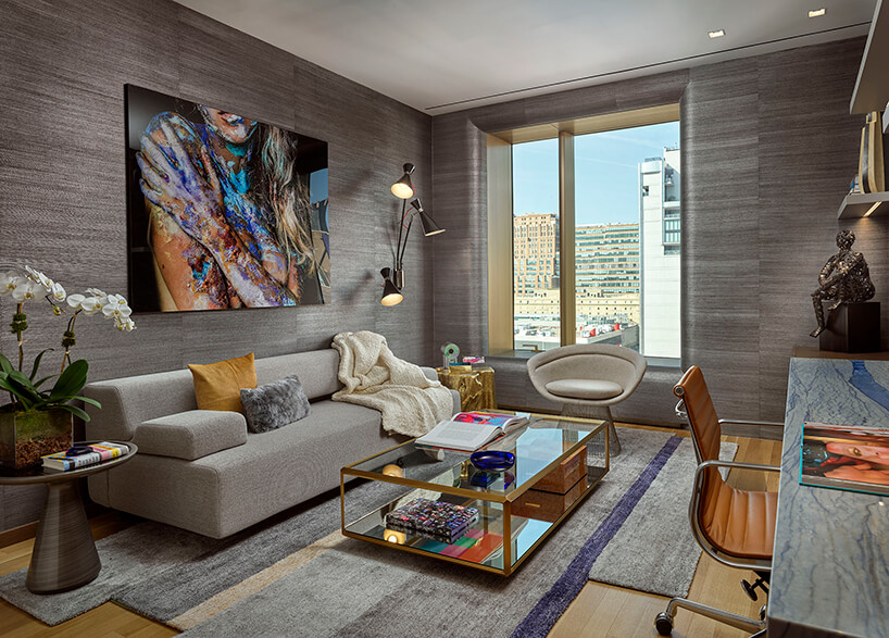 ekskluzywny apartament na manhattanie salon zszarymi ścianami dużym zdjęcie kobiety szklanym niskim stolikiem przed szarą sofą