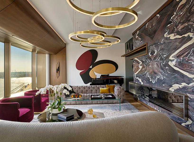 elegancki salon zwzorzystą ścianą iwyjątkowymi złotymi lampami wkształcie nachodzących okręgów