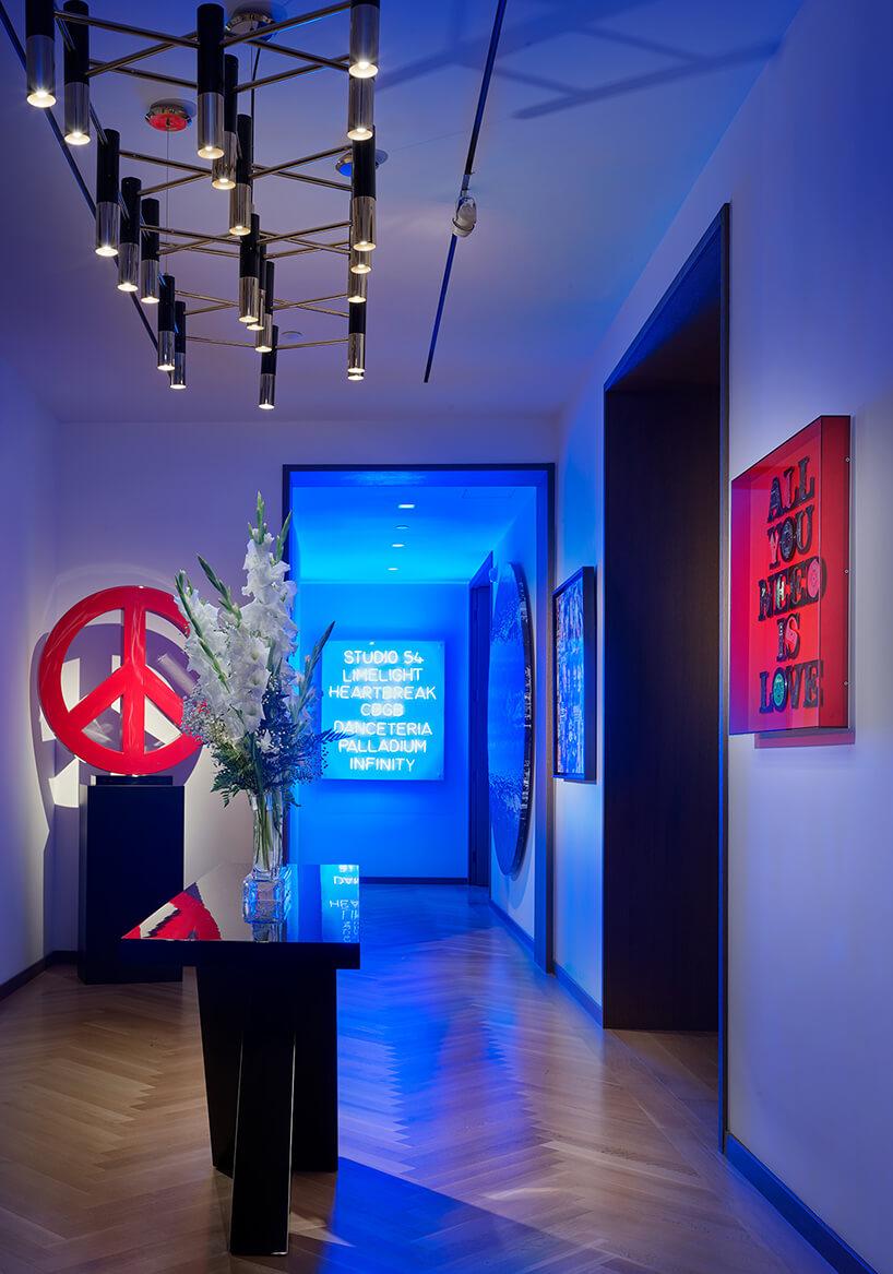 zdjęcie eleganckiego holu wniebieskim świetle idużą czerwoną pacyfką pod ścianą