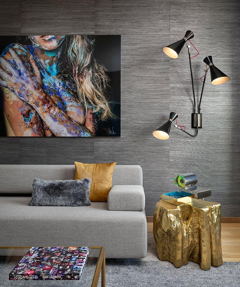 salon zszarą ścianą izdjęciem kobiety nad obok wyjątkowej lampy nad szarą sofą izłotym stolikiem wkształcie pnia