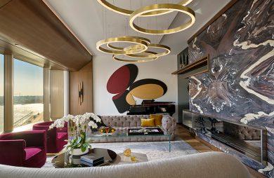 elegancki salon z wzorzystą ścianą i wyjątkowymi złotymi lampami w kształcie nachodzących okręgów