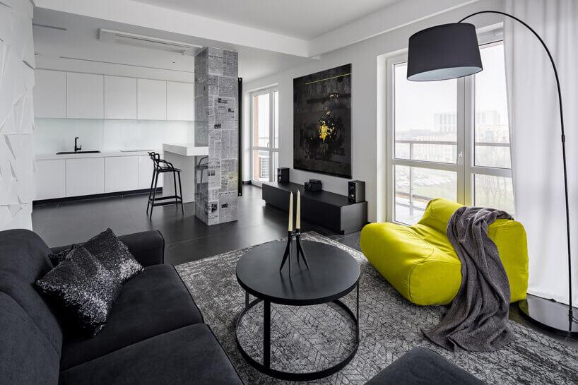 czarna kanapa lampa istolik żółty fotel na szarym dywanie