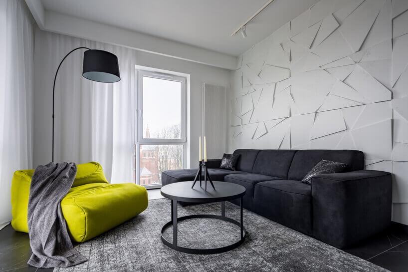 czarna kanapa lampa istolik żółty fotel na tle białej ściany