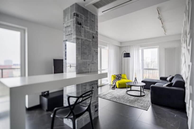 czarna kanapa krzesło lampa istolik żółty fotel na tle białej ściany