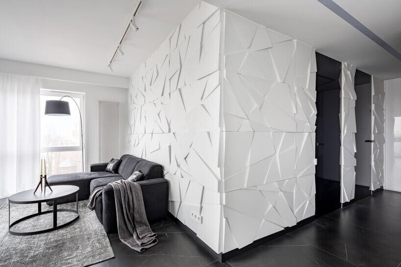 czarna kanapa lampa istolik na tle białej ściany