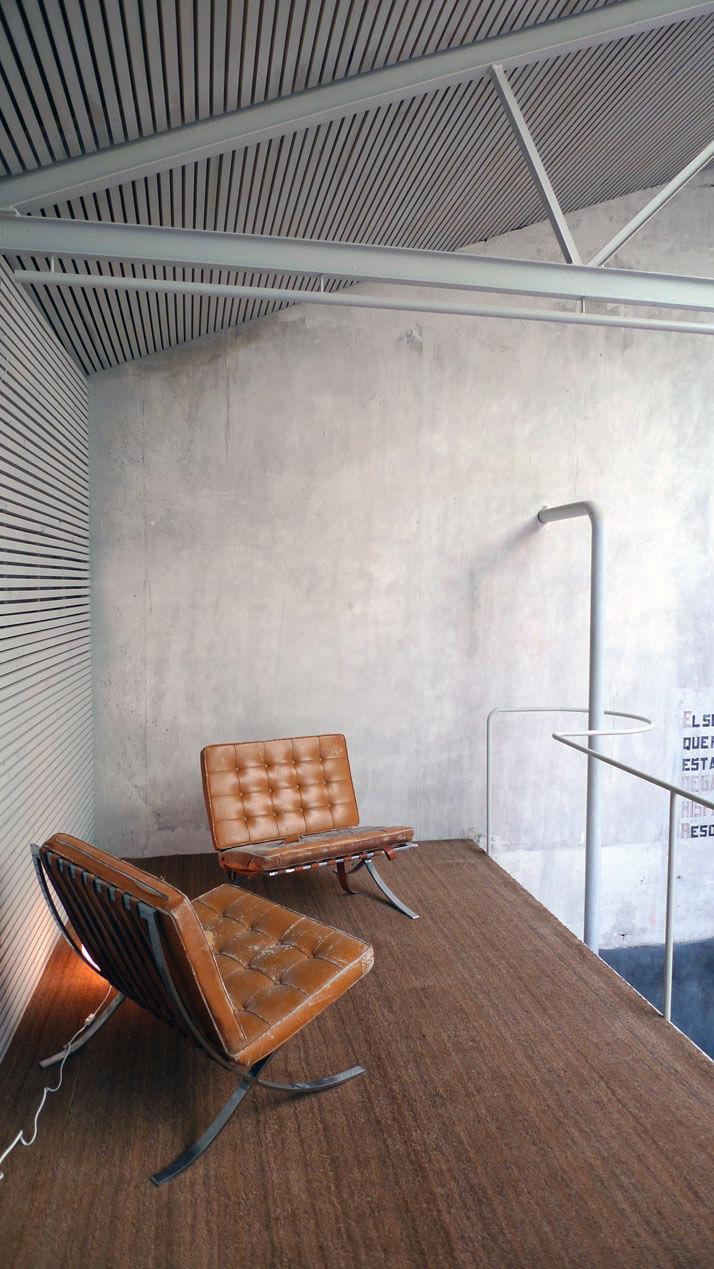 nowe postarzane brązowe fotele przy betonowej ścianie
