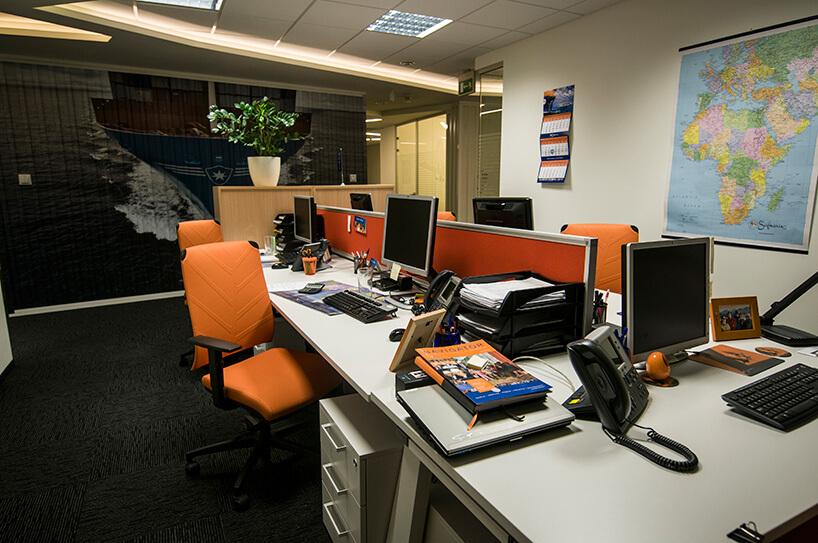 pomarańczowe krzesła wbiurze zkomputerami