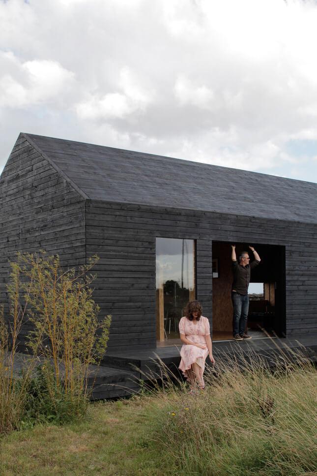 właściciele przy swoim ciemnym nowoczesnym domu
