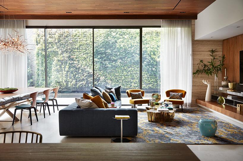 ekskluzywne wnętrze rezydencji od AEDI Interior salon zdużym oknem iniebieską sofą