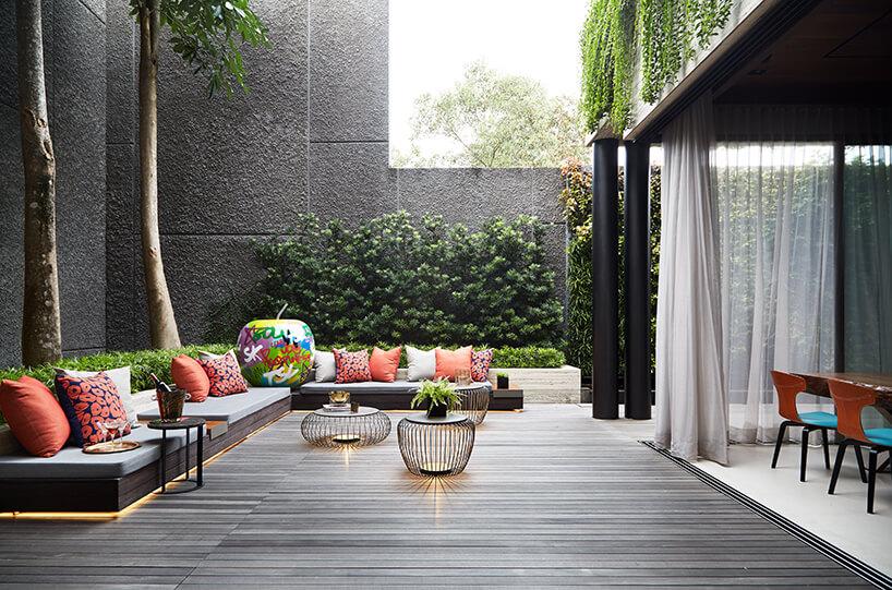 ekskluzywne wnętrze rezydencji od AEDI Interior szare osłonięte patio zdługim czarnym siedziskiem