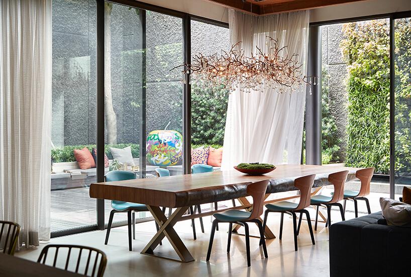 ekskluzywne wnętrze rezydencji od AEDI Interior duży drewniany stół zwyjątkowymi krzesłami pod żyrandolem wkształcie gałęzi