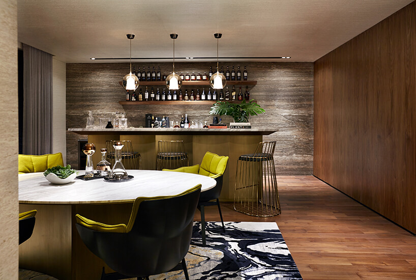 ekskluzywne wnętrze rezydencji od AEDI Interior duży stół zbiałym okrągłym blatem zczarno zielonymi krzesłami na tle baru zkamiennym blatem