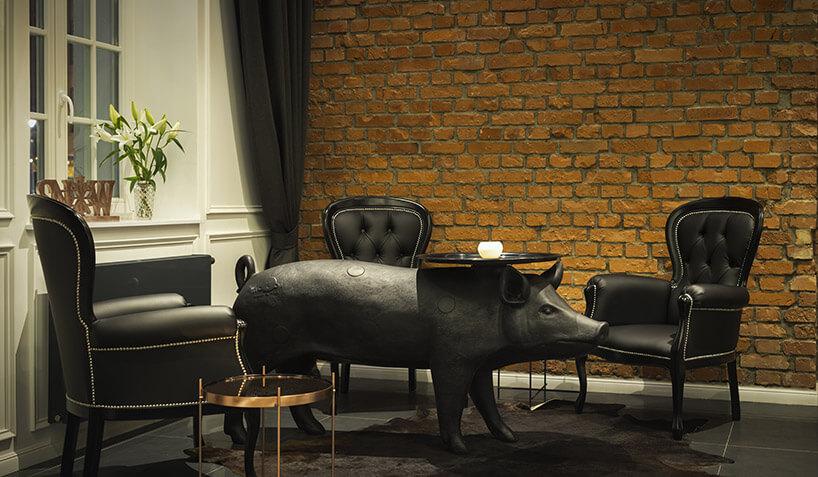 duży postument świni na tle ceglanej ściany