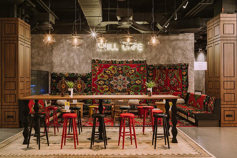 wnętrze hotelu ibis Styles Sarajevo od MIXD wysoki drewniany stół iwysokie stołki na tle dywanów na ścianie