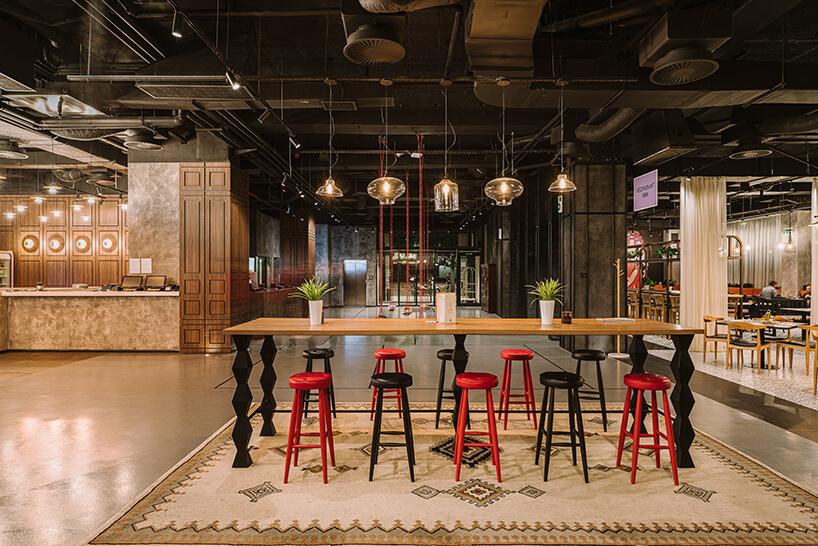 wnętrze hotelu ibis Styles Sarajevo od MIXD wysoki drewniany stół iwysokie stołki