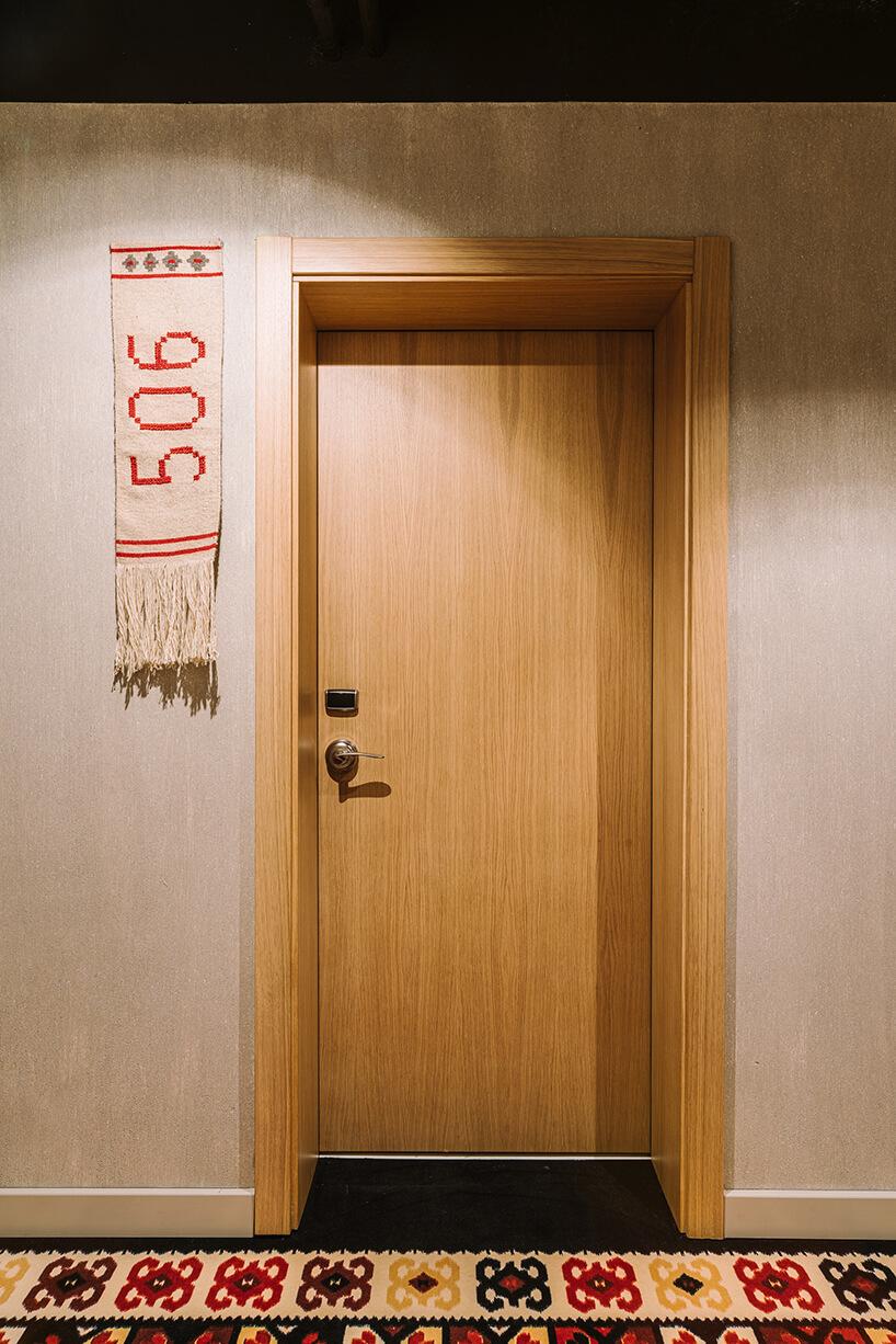 wnętrze hotelu ibis Styles Sarajevo od MIXD zdrewnianymi drzwiami do pokoju inumerem pokoju na szalu