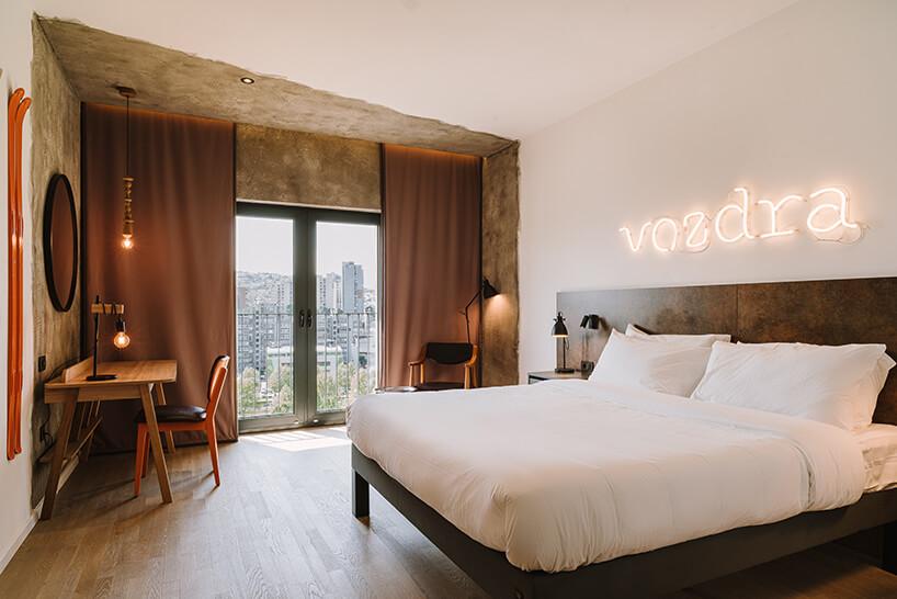 eleganckie wnętrze sypialni hotelu ibis Styles Sarajevo od MIXD zneonem nad łóżkiem