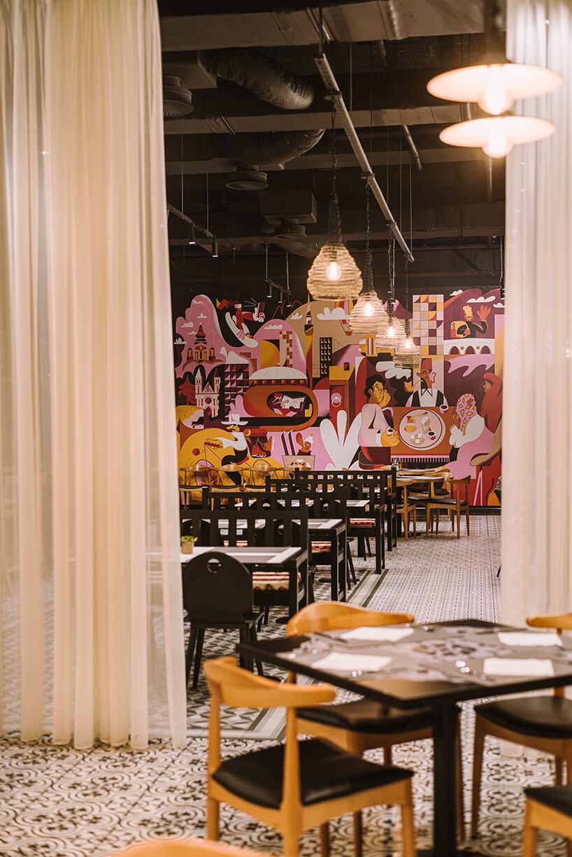wnętrze restauracji hotelu ibis Styles Sarajevo od MIXD zczarnymi stołami ikrzesłami na tle grafiki ściennej