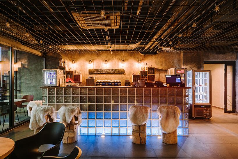 wnętrze baru ibis Styles Sarajevo od MIXD zkaflowym barem iskórami na stołkach barowych
