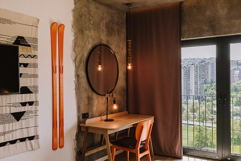 wnętrze pokoju ibis Styles Sarajevo od MIXD mały drewniany stolik ikrzesło obok pomarańczowych nart na ścianie