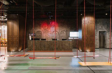 wnętrze hotelu ibis Styles Sarajevo recepcja i siedziska w podwieszonych na linkach deskach snowboardowych