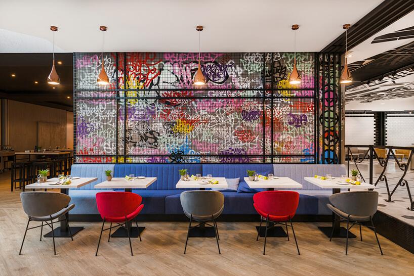 wnętrze hotelu Mercure Budapeszt od Tremend niebieska długa sofa ibiałe małe stoliki na tle ściany zgraffiti osłoniętą czarną siatką