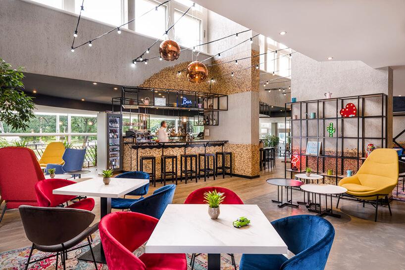 wnętrze hotelu Mercure Budapeszt od Tremend mały bar pośród białych stolików zkolorowymi krzesłami