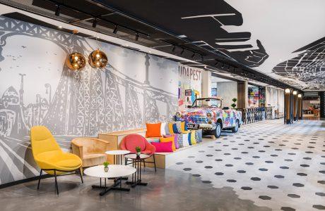 wnętrze hotelu Mercure Budapeszt od Tremend duży hol z małymi stolikami i kolorowymi krzesłami
