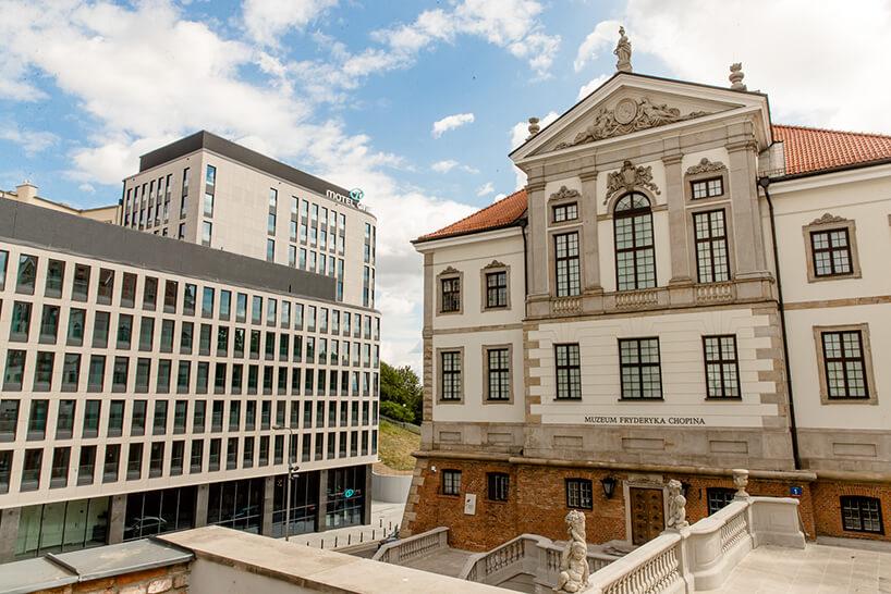nowoczesna bryła Motelu ONE obok zabytkowego Muzeum Fryderyka Chopina