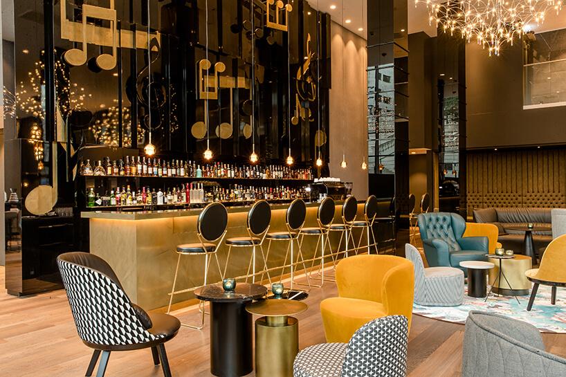 eleganckie wnętrze Motelu One cześć barowa zróznymi krzesłami przy małych stolikach inutami na czarnej ścianie za barem