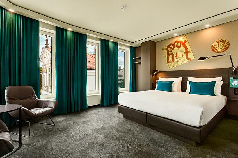 eleganckie wnętrze Motelu One pokój hotelowy zdwuosobowy łóżkiem wykończonym skórą iniebieskie zasłony obok widoku na klasyczny budynek
