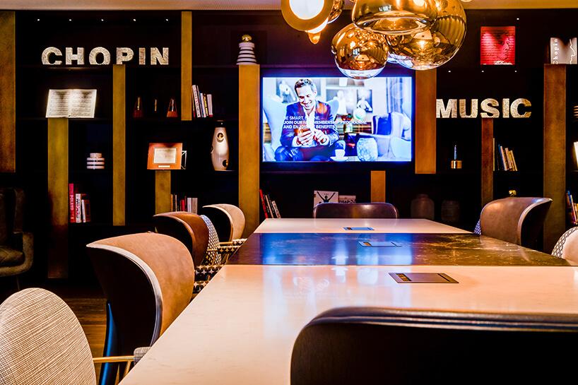 eleganckie wnętrze Motelu One długi stół zdwukolorowych blatów iróżnymi krzesłami