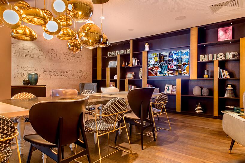eleganckie wnętrze Motelu One czytelnia wwyjątkowym żyrandolem ze złotych kul na tle ściany zzapisem nutowym utworu