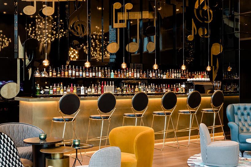 eleganckie wnętrze Motelu One czarno złote krzesła barowe przy wysokim barze