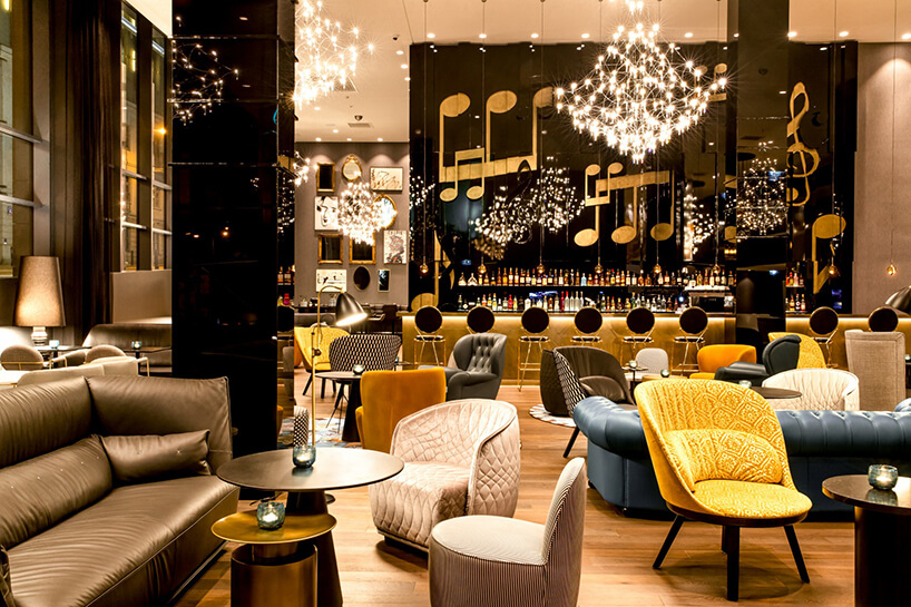 eleganckie wnętrze Motelu One stoliki wczęści barowej zróżnymi formami siedzisk ikolorów
