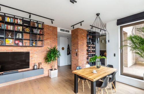 wnętrze w stylu hygge salon z ceglanymi ścianami małym stołem z drewnianym blatem i czterema czarnymi krzesłami