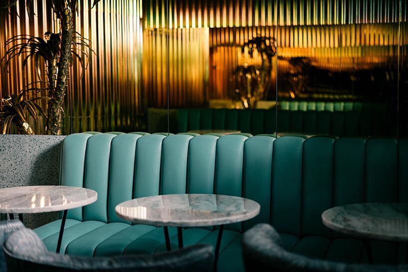 zielone sofy ifotele przy okrągłych małych stolikach wenątrz kilka stolików zzielonymi fotelami we wnętrzu Lukullus lodziarnia Warszawa