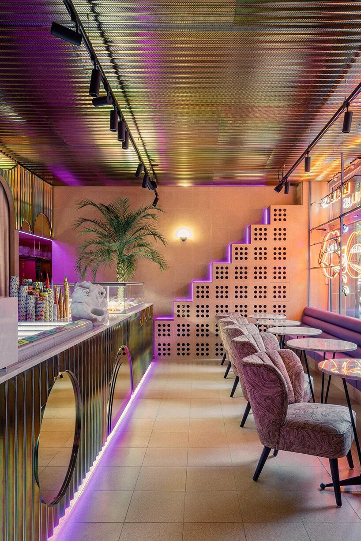 wnętrze kilka stolików zzielonymi fotelami we wnętrzu Lukullus lodziarnia Warszawa wpomarańczowym kolorze zbłyszczącymi wykończeniami lady isufitu